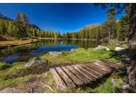 意大利蓝天下被岩石包围的湖泊和树木映照在_10303038