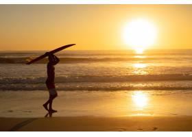 一名男子头顶着冲浪板在海滩上行走_5195375