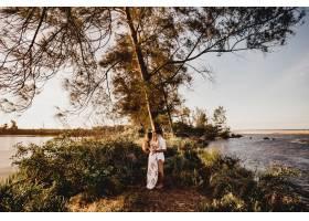 一对美丽的情侣在绿树成荫的衬托下的照片_13235032