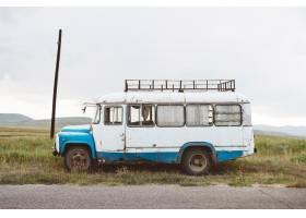 一辆老式小巴在多云天空下的绿色景观上的特_10186699