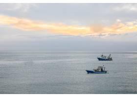 两艘船在多云的天空下横渡海洋的广角镜头_9931711