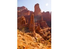 人们在白天走上沙漠悬崖附近山坡的垂直镜头_7810367