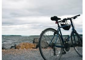 停放在多云天空下海边的蓝色山地自行车_10990455