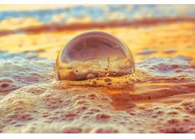傍晚日落时被大海包围的沙滩上透明球的特_10303177