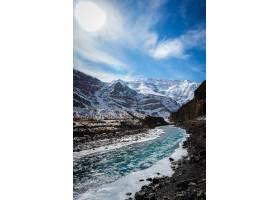 冰冻河流的垂直镜头背景是白雪覆盖的山脉_11358546