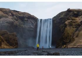 冰岛多云天空下被人和岩石包围的斯科加弗斯_9851727