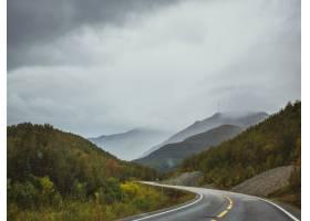 在乌云密布的天空下山里靠近森林的高速公_8943321