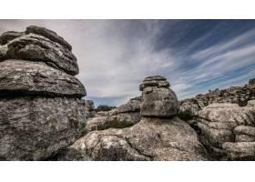 在多云的天空下几块灰色岩石堆积在一起的_9851508