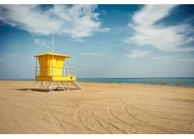 黄色救生员在空荡荡的海滩上站岗_11344824