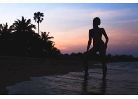 黎明时分站在海滩上的年轻美丽苗条的女人_10523502