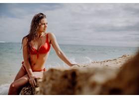 穿着红色比基尼的美女坐在岩石上在海滩上摆_10372282