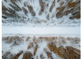 芬兰拍摄的被树木包围的积雪覆盖的道路的高_9184542
