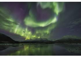 被白雪覆盖的群山环绕的湖面上北极光的美丽_9283369