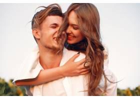 一对美丽时尚的情侣在向日葵的田野里_5713328