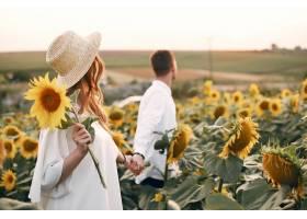 一对美丽时尚的情侣在向日葵的田野里_5713334