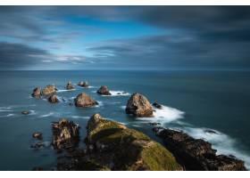 在蓝色多云的天空下水中有大石头的大海_9282830