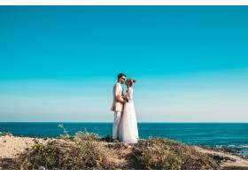 新娘和新郎在蓝天大海背后的悬崖上摆姿势_6799788