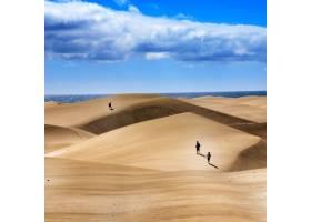 一群人在多云的天空下走在沙丘上_12449417