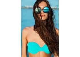 在阳光明媚的海滩上蓝色海水中戴着眼镜_9361780