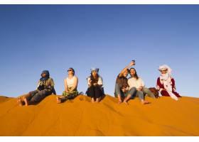 坐在沙丘顶上的一群人_4933530