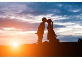 夕阳背景下甜蜜情侣接吻的剪影_1025907