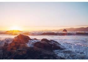 日落时海浪撞击海岸附近岩石的迷人景色_11061808