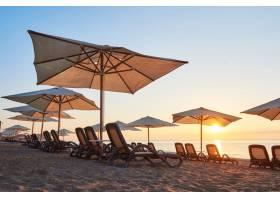 日落时海边有日光浴床的沙滩和群山的美景_10124006