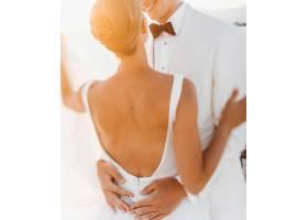 傍晚的阳光照耀着美丽的新婚夫妇他们在海_3984995