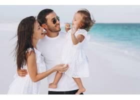 带着小女儿的年轻家庭在海边度假_5175746