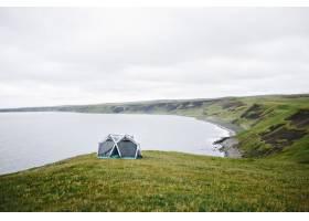 冰岛一名男子站在现代帐篷旁_11048884