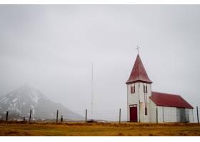 冰岛多云天空下田野上红色屋顶的老教堂_9991373
