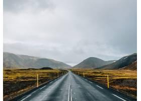 冰岛多云天空下被绿色和积雪覆盖的山丘包围_9970992