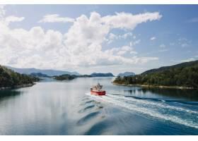 水面上的一艘船在晴朗的蓝天和白云下被树_7822760