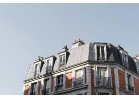 巴黎一栋带阳台的漂亮建筑屋顶的低角度拍摄_9077440