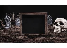 带着骷髅的黑色空牌子站在墓地上_2816927