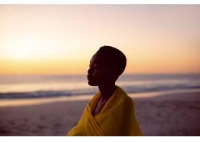 海滩上一位闭着眼睛围着黄色围巾的女子_5195088
