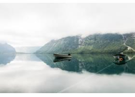 平静的湖面上孤零零的小船背景是雾蒙蒙的_4513645