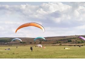滑翔伞的剪影在蓝天和云彩下飞过美丽的绿色_11179493