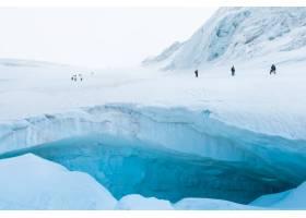 徒步旅行者在雪域陡峭的山上的探险_7810665