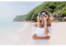 热情的欧洲女人穿着夏装仰望天空海滩上微_11365858