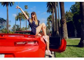 快乐易受影响的女孩举起手在红色敞篷车上摆_9842626