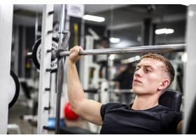 特写年轻男性在健身房进行手臂训练_6071372