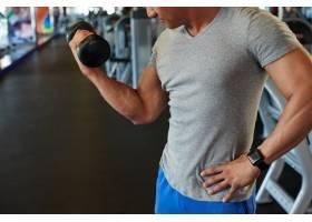 面目全非的健康男子在健身房用杠铃做二头肌_5839288