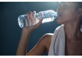 运动后的女性在健身房喝瓶子和手帕里的水_5470096