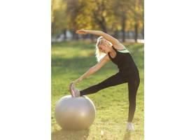 金发女子拿着健身球伸展身体_5938866