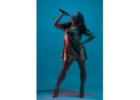 霓虹灯下隔绝在蓝色录音室墙上的女歌手肖像_13058311