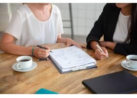 青年女同事开会讨论商业计划在纸上写战略_11081399