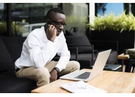 非洲裔非洲裔商人的手机笔记本电脑_3222576