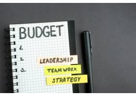 顶部视图预算笔记在记事本上暗面上有钢笔_13340897