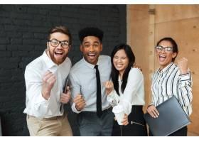高兴兴奋的年轻商业同事做出胜利者的手势_6514808